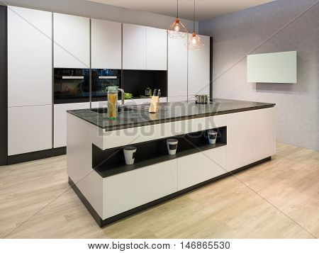modern flat white kitchen with cooking island and tv