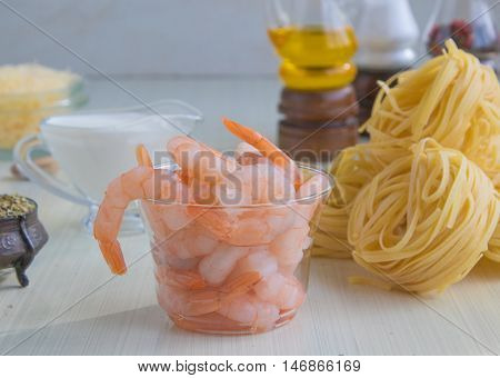 Ingredients for pasta with seafood - raw shrimps fettucine olive oil cream cheese parmesan and spices.