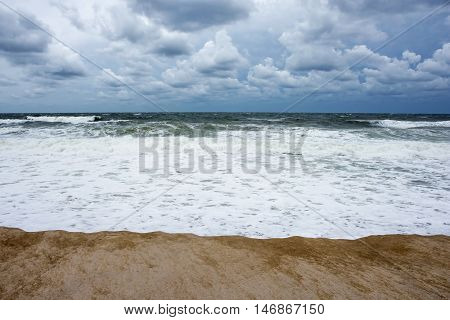 A stormy view along the Seaside Park NJ coastline with rough surf and dramatic clouds.
