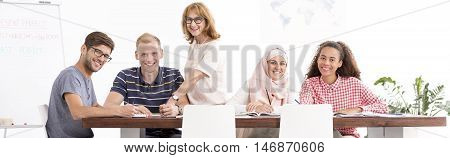 Shot of a smiling group of multicultural people sitting at a long desk and looking at a camera