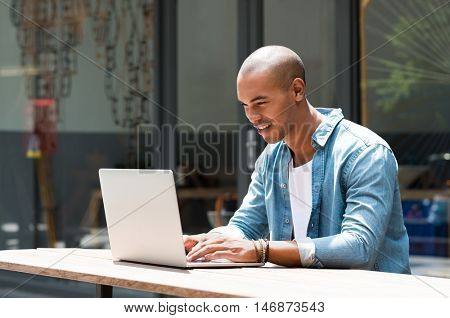 Happy man writing text on laptop in a modern coffee shop. Happy african student surfing the web on laptop with wifi free connection. Smiling guy in casual studying on laptop sitting outdoor the cafe.