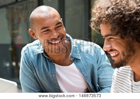 Close up face of best friends sitting and laughing. Happy african man smiling and looking at beard friend with curly hair. College students enjoying and relax outdoor.