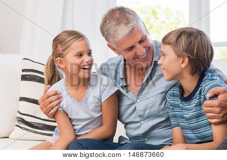 Smiling grandfather embracing his grandchildren on a sofa in living room. Happy grandpa playing with grandson and granddaughter on couch. Senior man in a conversation with boy and girl.