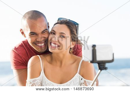 Portrait of happy couple taking selfie with selfie stick at beach. Smiling young multi ethnic couple using mobile phone to take picture. Smiling girlfriend and boyfirend in love using smartphone.