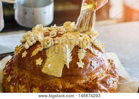 Brush touches decorated bread. Baked product on paper. Fresh wedding bread. Baker made a masterpiece.