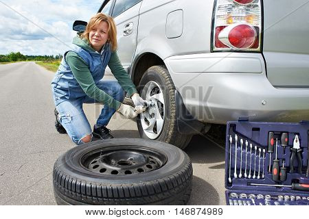 Woman Changing A Wheel Of Car