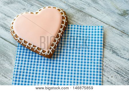 Glazed biscuit shaped as heart. Cookie on checkered napkin. Dessert for those in love. Find ways to show feelings.