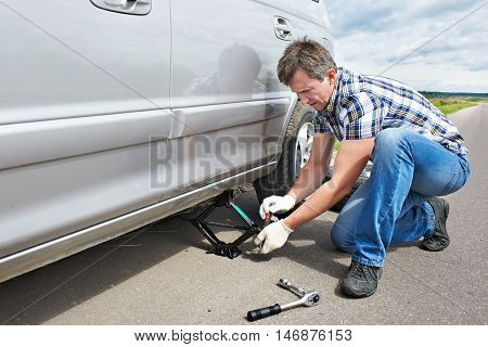 Man With Jack Changing A Spare Tire Of Car