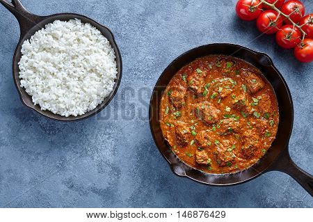Beef Madras curry slow cook Indian spicy chili butter lamb food with rice in cast iron pan on blue table background. Traditional India culture restaurant dish.
