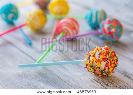 Bright candy on a stick. Cake pop with icing. How to make children happier. White chocolate and cream filling.