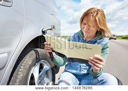 Woman Reading Owner's Manual Of Car