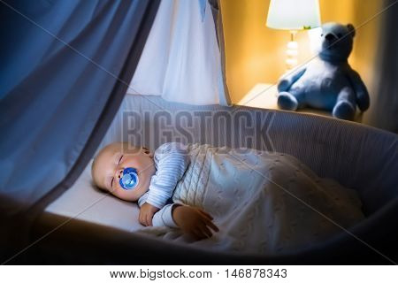 Adorable baby with pacifier sleeping in blue bassinet with canopy at night. Little boy in pajamas taking a nap in dark room with crib lamp and toy bear. Bed time for kids. Bedroom and nursery interior.