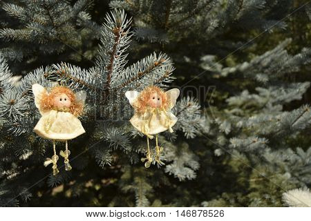 Christmas toys in the form of angels. Toys are located on a fir-tree. Angels in white clothes. Angels have golden hair