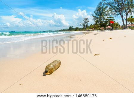 Old plastic bottle on a beautiful tropical beach in Indonesia. Pollution concept.