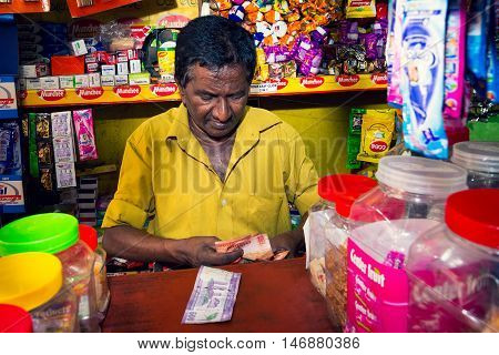 COLOMBO SRI LANKA - FEBRUARY 16 2016: Unidentified seller counting money on Colombo market.