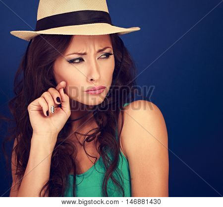 Annoyed Suspicious Woman In Straw Hat Looking With Hand Near Face On Blue Background. Toned Closeup