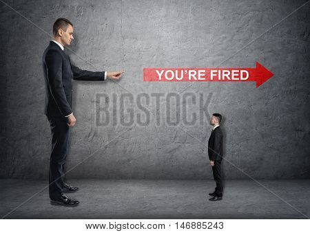 Big businessman poiting at red arrow with 'you're fired words' over small businessman. Losing a job. Unemployed. Jobless. Discharging.