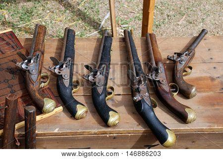 Replica Antique black powder Flint Lock Pistols on a wooden bench