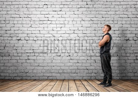 Front view of muscled young man looking up, on the background of white brick wall. Wellbeing. Muscleman. Workout and fitness.