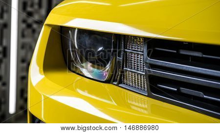 Car detailing series : Closeup of clean yellow car headlights