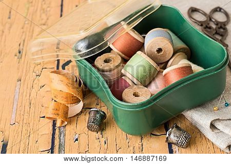 Box with a spools of thread, a piece of fabric, scissors and thimbles on an old wooden table.