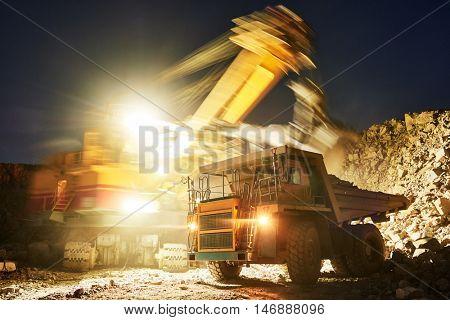 Mining. excavator loading granite or ore into dump truck poster