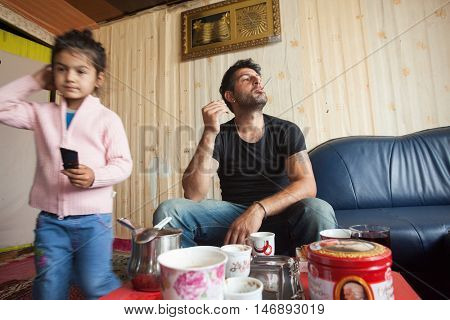 ZAGREB, CROATIA - OCTOBER 21, 2013: Roma man and his daughter at their home.