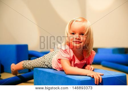 Cute Little Blond Girl Lying On Floor In Playing Room.