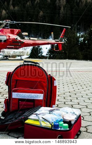emergency bag and rucksack with medical devices near a rescue helicopter