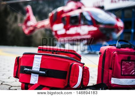 emergency bags and rucksacks with medical devices and a rescue helicopter