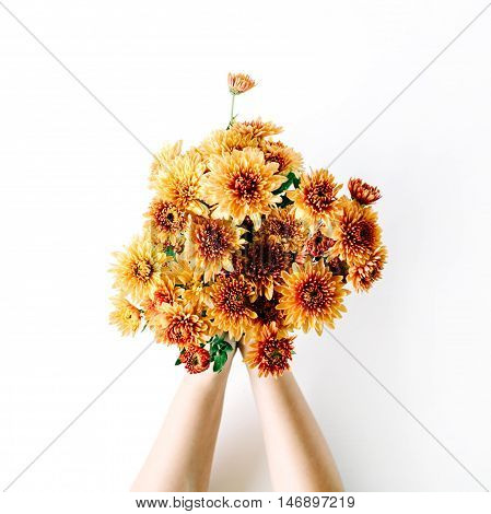 chrysanthemum bouquet in girl's hands on white background. flat lay top view concept