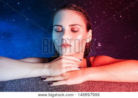 Closeup portrait of young woman beauty in pool during rainy evening