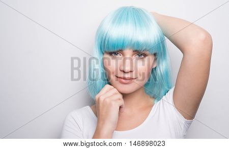 Cheeky young girl in modern futuristic style with blue wig smiling and looking into the camera with her hands on head over white wall background with copyspace
