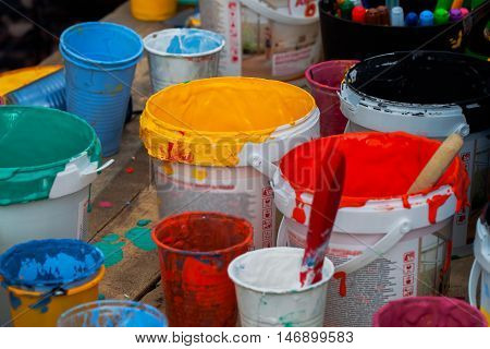 Acrylic paints palette and painted brushes on wood background stained with various color. Children's creativity. Can be used for bright backdrop