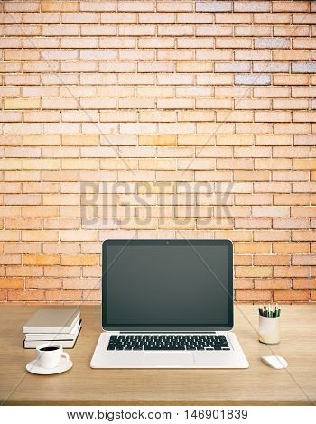 Creative designer workplace with blank laptop computer coffee cup book supplies and other items on red brick wall background. Mock up 3D Rendering