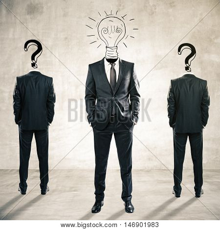 Two question mark headed businessmen behind light bulb headed man on concrete background. Idea and leadership concept