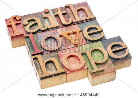 biblical, spiritual  or metaphysical reminder - faith, hope and love - word abstract in letterpress wood type blocks, stained by colorful inks, isolated on white