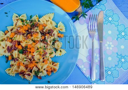 Italian Wholemeal Pasta Farfalle Butterfly Bow-tie with Butternut Squash and Prosciutto. Pasta with pumpkin sauce, bacon and fresh parsley on blue wooden background. Italian cuisine concept. Top view.