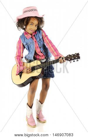 A full-length image of a young cowgirl happily strumming a classical guitar.  On a white background.