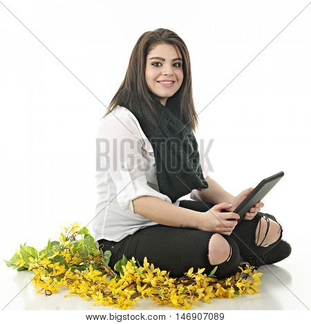 A pretty teen girl happily looking up from the iPad she holds while sitting among forsythias.  On a white background.