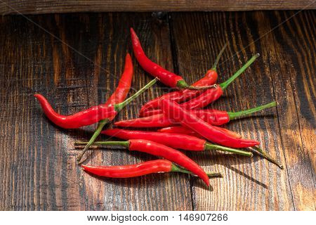 Pile of thai Bird's Eye Chilis on a old wooden table. Very hot seasoning
