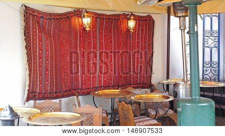 Moroccan Style Cafe With Brass Tables and Carpet at Wall