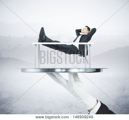 Hand in glove holding abstract silver tray with relaxing businessman on landscape background