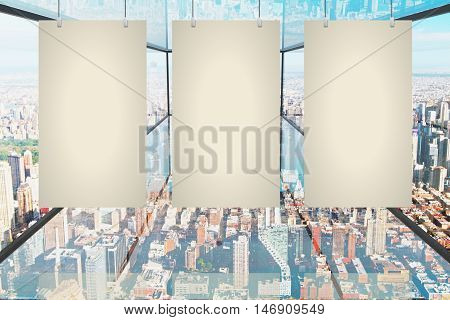 Three blank canvas hanging in abstract transparent glass room with city view. Mock up 3D Rendering
