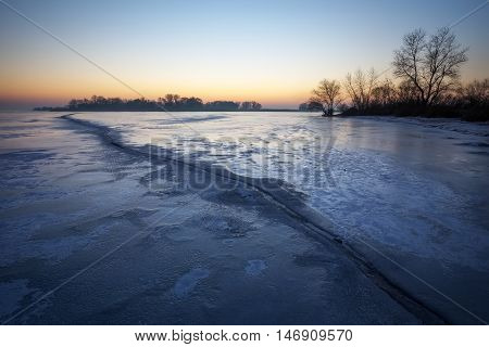 Winter landscape with frozen lake and sunset sky. Composition of nature.