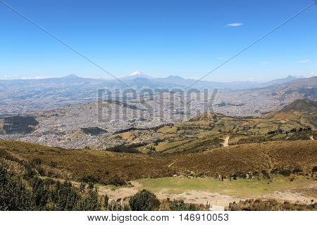 This photo shows a view of the valley of Quito city with Cotopaxi Volcano in the background. It was taken from the cableway station.