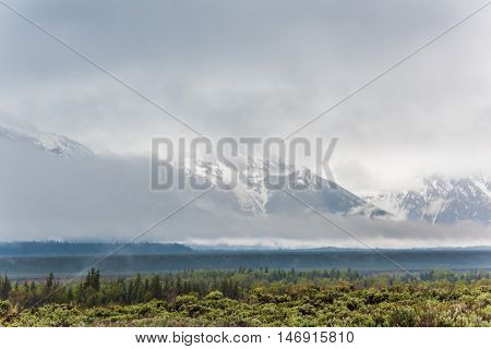 Grand Teton mountains covered with fog and dark storm clouds