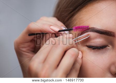 Master corrects makeup gives shape and plucks previously painted with henna eyebrows in a beauty salon.
