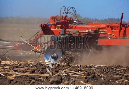 Large tractor pulling a plow and plow the field remove the remnants of the previously beveled sunflower. The work of agricultural machinery.