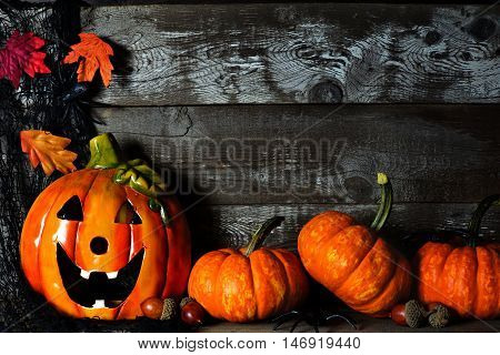 Halloween Jack O Lantern At Night With Pumpkin Corner Border Against A Rustic Old Wood Background